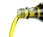 Pouring extra virgin olive oil from glass bottle on white background Stock Photo