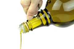 Pouring extra virgin olive oil from glass bottle on white background Stock Photos