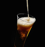 Pouring foam into a glass of cold beer on a black background Stock Images