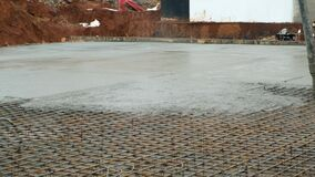 Pouring foundation with wet heavy concrete through pipe on costruction site.
