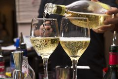 Pouring franciacorta. Horizontal closeup of a barman pouring  two glasses of franciacorta, italian wine,  on the bar counter royalty free stock images