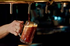 Pouring fresh alcoholic beverage. Batender hand pouring fresh ale beer in glass from beer tap in pub or restaurant Stock Photos
