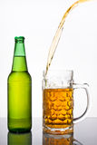 Pouring beer into mug. Pouring fresh beer into a mug, motion shot with green bottle Royalty Free Stock Photos