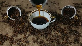 Pouring fresh brewed coffee into the coffee cup. Fresh aromatic coffee being poured into coffee cup from cezve turkish coffee pot on background of bagging and stock video footage