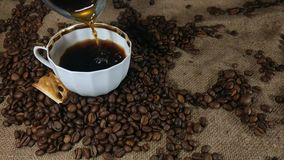 Pouring fresh brewed coffee into the coffee cup. Barista`s hand pouring fresh aromatic coffee  into coffee cup from turkish coffee pot on background of bagging stock video
