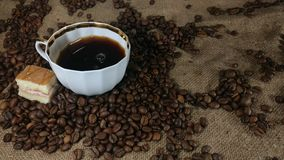 Pouring fresh brewed coffee into the coffee cup. Barman`s hand pouring fresh aromatic coffee  into coffee cup from turkish coffee pot on background of bagging stock footage