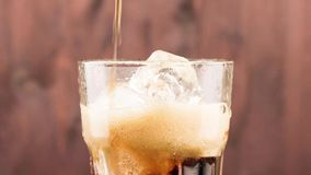 Pouring fresh coke with ice cubes isolated on wood background stock video