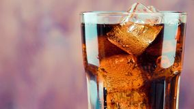 Pouring fresh coke with ice cubes isolated on wood background stock footage