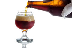Pouring fresh cold beer into glass goblet Royalty Free Stock Images