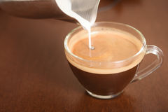 Pouring fresh milk into cup of coffee Stock Photography