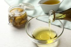 Pouring fresh olive oil into bowl. On table stock photo
