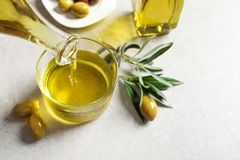 Pouring fresh olive oil into glass royalty free stock photos
