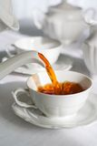 Pouring fresh tea. Pouring fresh tea from porcelain tea kettle into white cup. Focus on tea stream, shallow depth of field Royalty Free Stock Photo