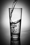 Pouring fresh water. Captured action of pouring fresh water in the glass on white background with dark corners. Black and white Stock Images