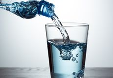 Pouring water from bottle into glass. Pouring fresh water from bottle into glass stock image