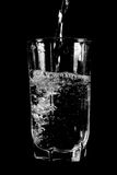 Pouring fresh water in faceted glass. Royalty Free Stock Photography