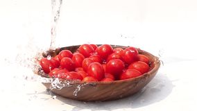 Pouring fresh water on a pile of cherry tomato in a wooden bowl on white background