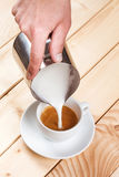 Pouring frothed milk into a cup of coffee Royalty Free Stock Image