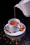 Pouring fruity tea close-up. Black background Stock Photography