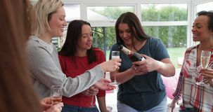 Pouring a Glass of Champagne. Small group of female friends celebrating with a glass of champagne. A woman is pouring the champagne from the bottle into the stock video