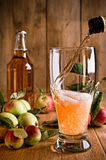 Pouring Glass of Cider. Pouring a glass of cider with apples and bottle on rustic wooden background royalty free stock photo
