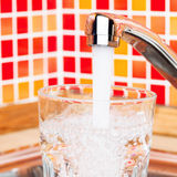 Pouring a glass with drinking water from kitchen tap Royalty Free Stock Photo
