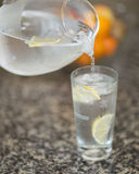 Pouring a glass of ice water. A glass container of lemon ice water pouring into a glass on granite counter Royalty Free Stock Photos