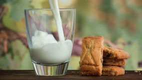 Pouring glass of milk and cookies stock footage