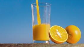 Pouring a glass of orange juice creating splash stock video