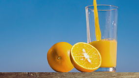 Pouring a glass of orange juice creating splash stock video footage