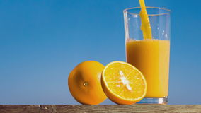 Pouring a glass of orange juice creating splash. Slow motion stock footage
