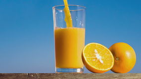 Pouring a glass of orange juice creating splash. Slow motion stock video