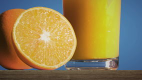 Pouring a glass of orange juice creating splash. Slow motion stock video footage