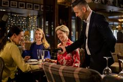 Pouring a Glass of Prosecco. Mature waiter pouring a glass of prosecco for a table with three mature women sitting, laughing and smiling stock photos