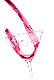 Pouring a glass with red cocktail tilted and splashing Royalty Free Stock Image