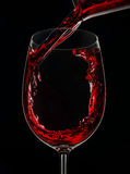 Pouring a glass of red wine. On black background stock photo