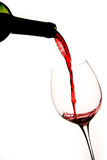 Pouring a Glass of Red Wine. With White Background Stock Photo