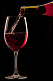 Pouring a glass of red wine on black background Royalty Free Stock Images