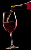 Pouring a glass of red wine on black background. Stock Images