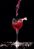 Pouring a glass of red wine at the black background Royalty Free Stock Photos