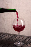 Pouring a glass of red wine. Closeup of the neck of a wine bottle pouring red wine into a wine glass on a rustic wooden table royalty free stock photos