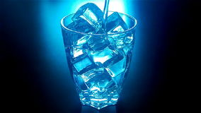 Pouring glass of water with ice cubes with blue backlit in slow motion at 120fps