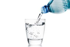 Pouring a glass with water trough little blue bottle and space for text Stock Photo