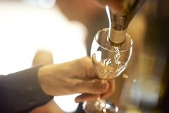 Pouring a glass of white wine. A waiter pours a glass of white wine Stock Photos