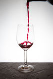 Pouring a glass of wine. Wine glass on fancy table top with white back lighting. Red wine splashing around in bottom of glass Stock Image