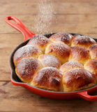 Pouring glasse sugar in brioche ball pie in a pan Royalty Free Stock Photos