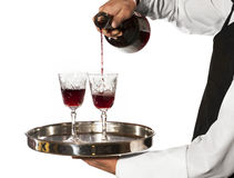 Pouring glasses of wine. Waiter pouring glasses of wine isolated on white royalty free stock photography