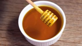 Pouring golden sweet honey on white bowl ceramic with a wooden honey dipper on wood table. Honey is a sweet, sticky, golden fluid made by bees stock video
