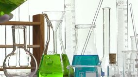 Pouring green liquid in a  Erlenmyer flask using a funnel. Ambiance performed with various laboratory containers on white background stock footage