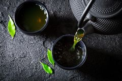 Pouring green tea into cup on rock Stock Photography